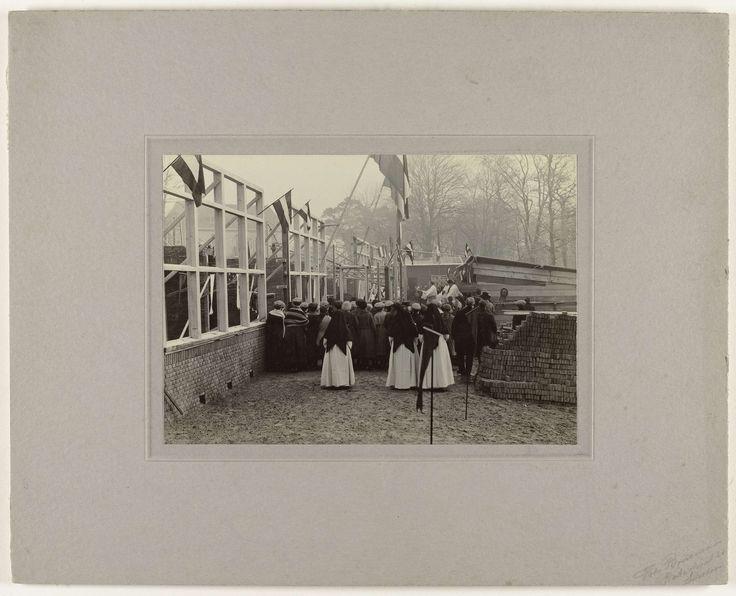 Anonymous   Inzegening lagere school, Anonymous, 1920 - 1930   Bij een school in aanbouw zijn katholieke geestelijken bezig de school te zegenen. Op de voorgrond een paar nonnen, daarachter kinderen. Aan de kozijnen hangen Nederlandse vlaggen.