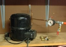 Vacuum Pump - Homemade vacuum pump adapted from a surplus refrigerator compressor. Incorporates an inline vacuum gauge.