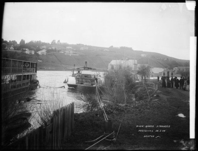 Wanganui, and Whanganui River, during the floods of May 1904. Shows stranded river boats, including the Manuwai (centre). On the right is a group of onlookers, with a flooded street in the distance. Photograph taken by Frank J Denton, circa 26 May.