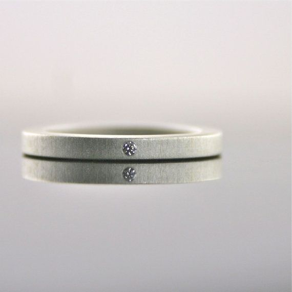 Handmade matte finish sterling silver ring with one tiny sparkling diamond flush set.    The ring measures approximately 2 mm wide and 2 mm thick.