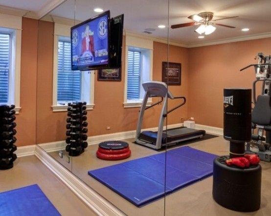 La sala de ejercicio tiene in equipo de ejercicio mucho. La acera tiene un espejo.