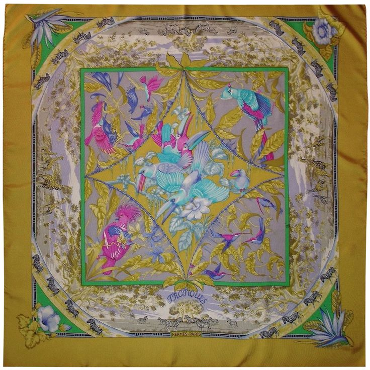 """Hermes scarf beautiful, titled """"Tropics""""  - Created by Laurence Bourthoumieux  - 1987 edition  - 100% silk, beautiful yellow, purple, fuchsia, green ...  - Dimensions: 89cm x 90cm  - The care label is missing  - Scarf collection  - Sort the laundry  - It will be delivered without its original box  - Very good state  - Tiny son learned a halo and a few inconspicuous spots"""