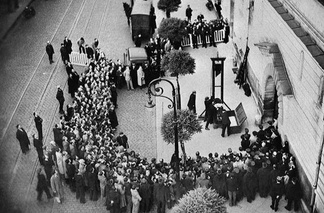 The Last Public Execution By Guillotine 1939--Above, we can see the guillotine's blade about to claim the head of Eugen Weidmann. Weidmann was a robber and a murderer before he eventually got caught and sentenced to death. On June 17, 1939, entire crowds turned up to see the gory spectacle.