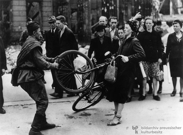 A German woman defends her bicycle from a Soviet soldier, 1945. In 1945, bicycles were a coveted means of transportation. Here, a Soviet soldier attempts to wrest a bicycle from a German woman in Berlin since a special …permission was required to use a bicycle.