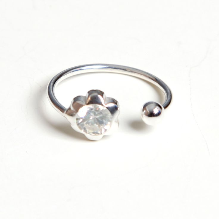 Anillo de Plata de Ley. Diseño sencillo y actual abierto con una pequeña bola en un extremo y circonita en forma de flor en el otro. El anillo se adapta a cualquier dedo. Todas nuestras joyas se envían en cajita listas para regalar.