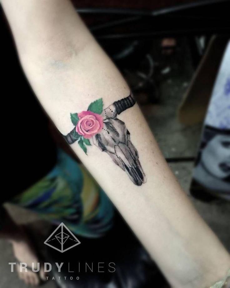Little bull skull tattoo on the inner forearm.