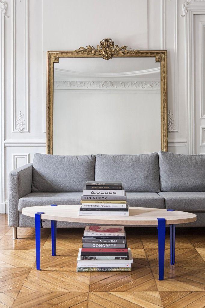 salon avec un canapé gris, un miroir en guise de déco et une table ronde avec des pieds de table bleu indigo