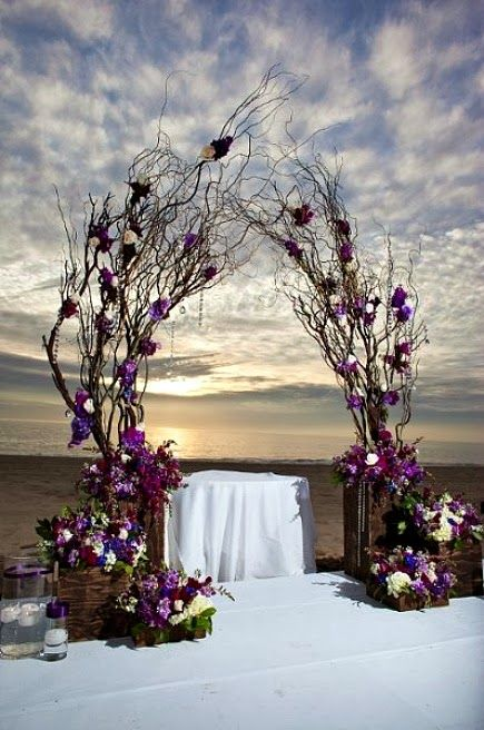 Arch made out of dry branches decorated with flowers in mauve, and then add a central table.