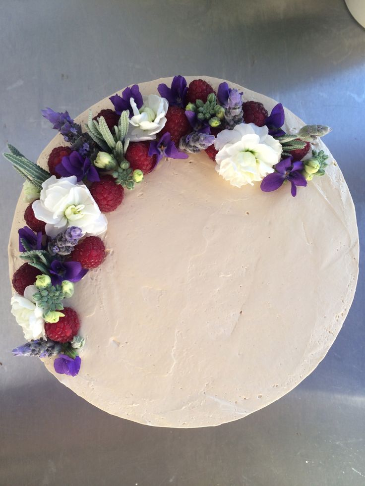 A very simple cake decorated with fresh berries and blooms