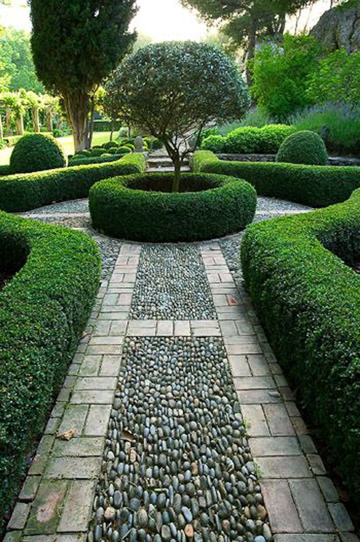 Round pebbles in the path work well with the rounded box hedging. Giving this garden structure but softer than it would be with straight lines.