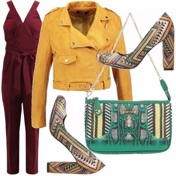 La tuta bordeaux con scollo profondo e cintura in vita è resa sportiva dal giubbotto di pelle gialla con chiusura a zip. Le scarpe e la borsa a fantasia richiamano i colori basici dell'outfit.
