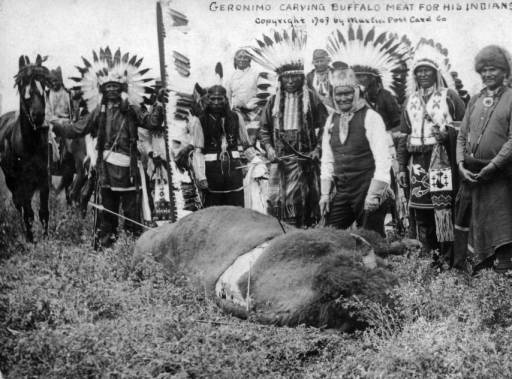 Geronimo carving buffalo meat for his Indians :: 1909