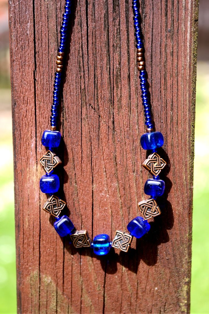 Kelt v modré Náhrdelník je tvořen rokajlem v modré a měděné barvě a mezičlánky s keltským vzorem. Zapínání na karabinku. Délka náhrdelníku je 51cm.