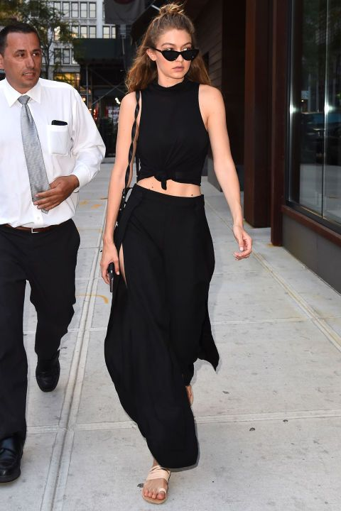 In a knotted black crop top, thigh-high slit trousers, strappy nude sandals and black cat-eyed sunglasses in New York City.