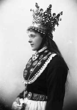 Digitalt Museum - Studiofotografi av kvinne med brudedrakt og brudekrone fra Sogn. Utslått hår. Hofteutsnitt. Vendt mot venstre. Ser ut mot venstre.