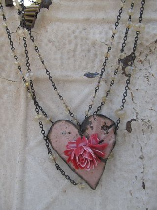 Heart Necklace by Tricia Samsal with Bobby Boyd Designs.  At first I thought this was a bit of antique wallpaper. But instead it looks like painted tin with a 3d flower on it.  Cute.