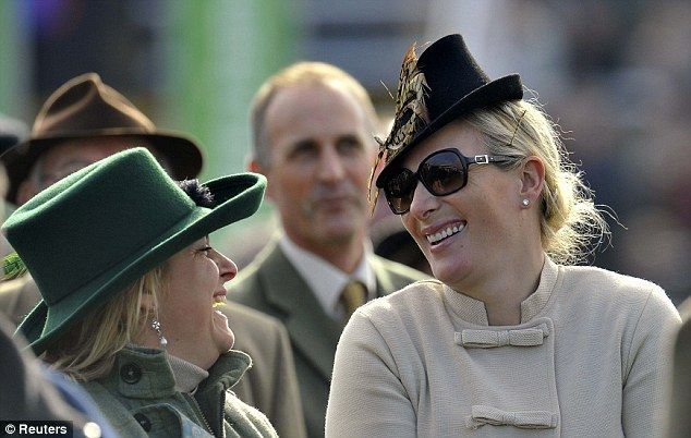 Zara has a giggle with a friend at the Cheltenham races today 11 Mar 2014