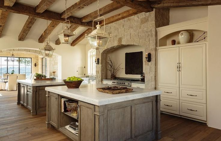Mediterranean kitchen features a vaulted ceiling lined with rustic wood beams and distressed gray carriage lanterns hanging over side by side islands topped with carrera marble atop a wide plank wood floor.