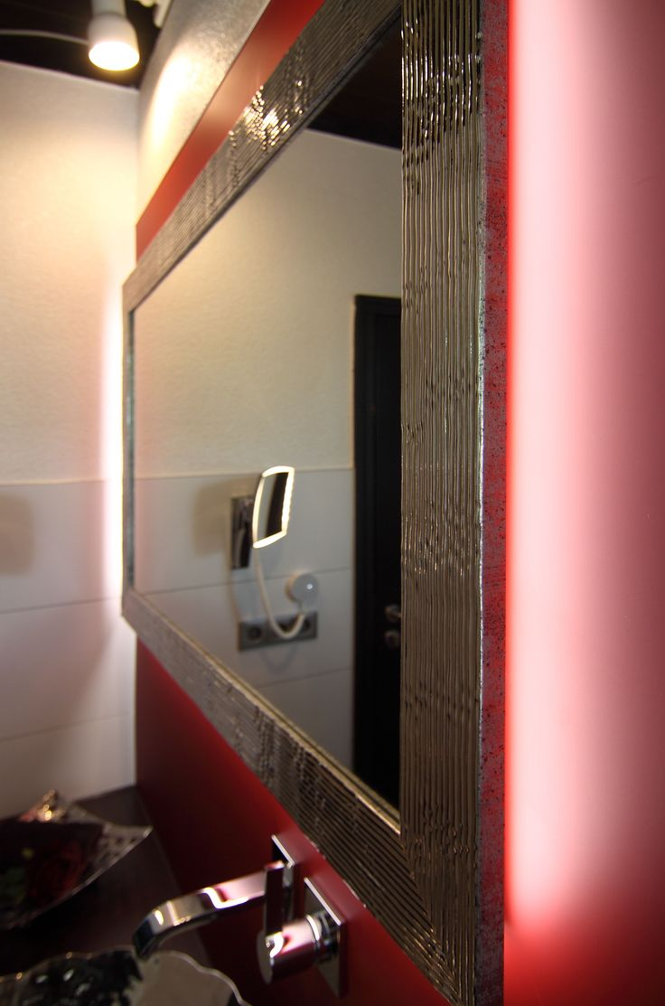 Mit der integrierten Spiegelbeleuchtung wird die rote Rückwand angestrahlt