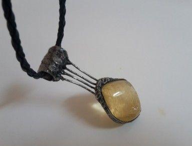 Valoun citrínu, 2,5 cm velký zasazený v cínu. Celý přívěsek je dlouhý 6 cm a je zavěšený na koženkovém splétaném řemínku. Citrín náleží planetě Slunce, elementu ohně a má projektivní energii. Mimořádně blahodárně působící krystal, je to šťastný a štědrý kámen. Je jedním z kamenů hojnosti, učí nás přilákat k sobě bohatství, prosperitu a úspěch, poskytuje štěstí každému, kdo ho vlastní. Předchází nočním můrám a zajišťuje příjemný spánek.
