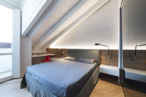 """Monza, Appartamento privato. La camera da letto: la testata """"custom"""" che sostiene i comodini a balzo accoglie una LED strip su misura che lava la parete e due lampade parete (cortesia: Brian Sironi)"""