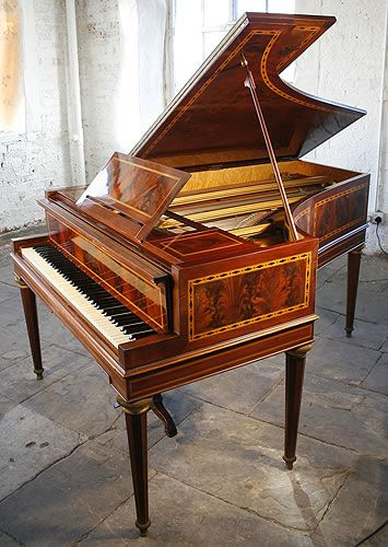 An art cased, Erard grand piano with an inlaid, mahogany case. Cabinet features stunning flame mahogany panels accented by satinwood crossbanding inlaid with diamond ebony detail. Piano has six tapered, octagonal legs with stringing inlay and brass finials. Piano lyre has claw and ball feet. A replica of Marie Antoinette's piano.  #uniquepiano #artcasedpiano