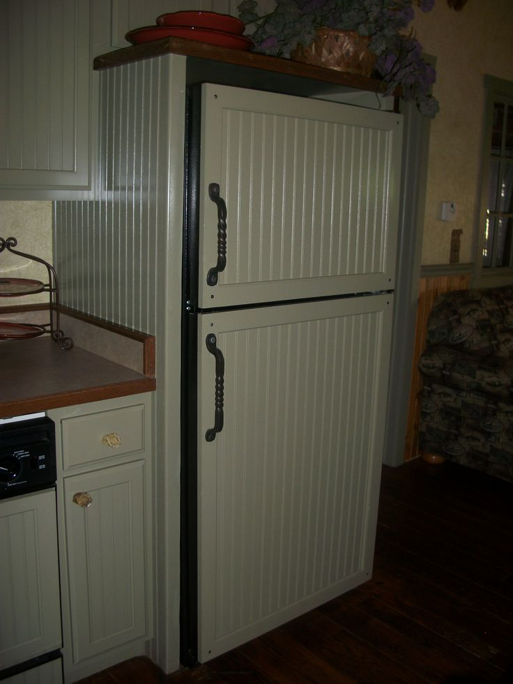 Covering the black refrigerator with wainscoting panels to lighten the kitchen
