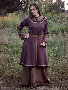 """Anglo-Saxon England 449 to 1066 AD - The tunic ended between the hip and the knee and had either long or short sleeves. Clasps were not needed to hold the tunic together because when pulled over the head it would sit snugly around the neck without the use of lacing or ties, indicating that the garment was one continuous piece. A belt or girdle was usually worn with the tunic and might have had a buckle, and, as Owen-Crocker states, """"pouched over the belt"""".[8]"""