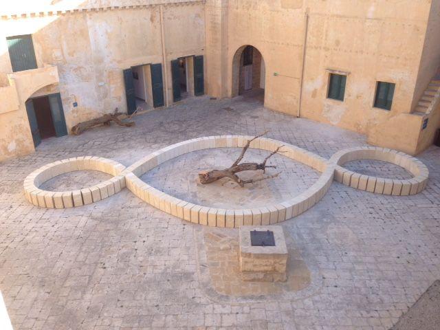 """Il """"Terzo Paradiso"""" allestito nella Piazza d'armi del castello di Gallipoli al cui centro è stato posto un grande ceppo di ulivo dentro al quale germoglierà un ulivo neonato"""