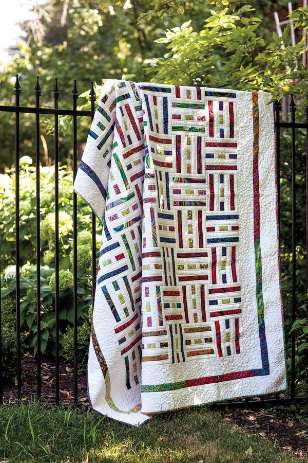 Brightly colored fabrics weave through a white background in this cleverly designed quilt. Make the quilt blocks in sets of nine, seven, and six to replicate the woven structure. This quilt is fat-quarter friendly.
