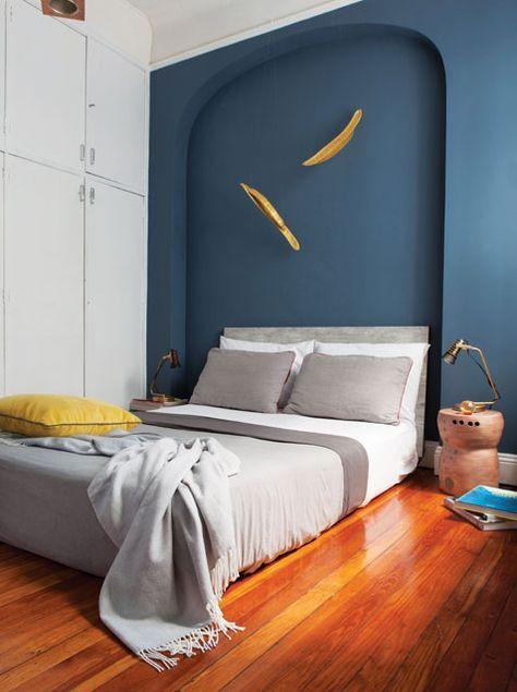 Dormitorio de un departamento en el microcentro porteño con cama de dos plazas, sábanas blancas (Arredo) y un plumón gris de Roberta Allen (Falabella).