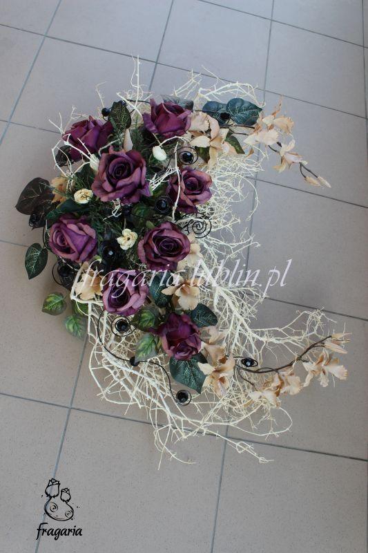 """Wyjątkowy stroik prezentowany na zdjęciach jest zaprzeczeniem wielokwiatowej kompozycji, gdyż składa się głównie z suszu """"ubranego"""" w osiem róż i dwa storczyki. Kwiaty uzupełnione są niewielka ilo..."""