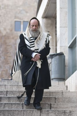 An orthodox Jew en route to synanogue. Jerusalem is a preferred home of religious Jews. Churches, mosques, synagogues, and religious schools are part of the cityscape.