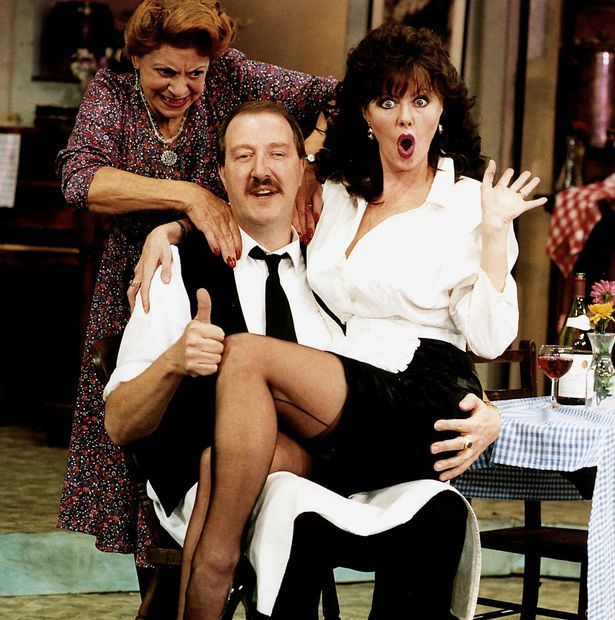 Allo Allo comedy series about the french resistance starring Gordon Kaye actor as cafe owner Rene Carmen Silvera actress as his wife and Vicki Michelle actress as waitress Yvette sitting on his knee