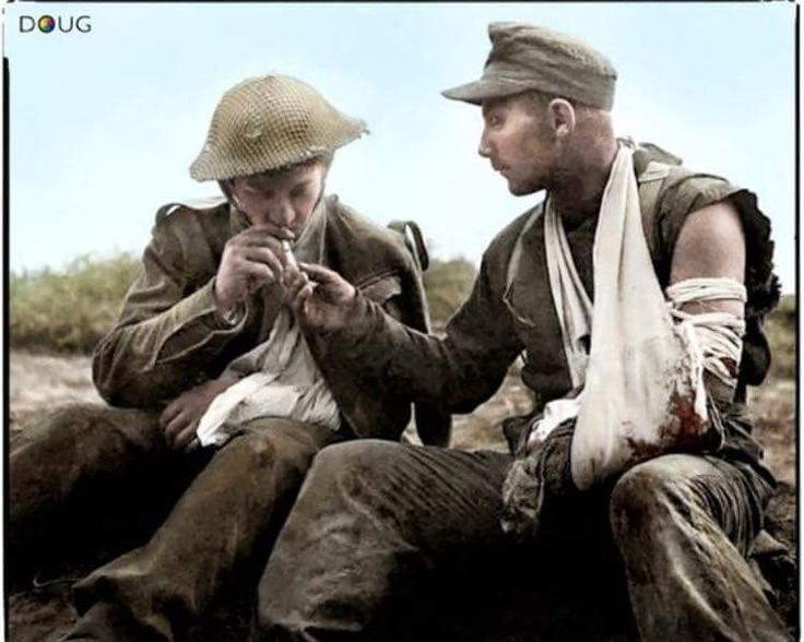 2 wounded soldiers share a light. 1 is from the Durham Light infantry the other is a Deutsches Afrikakorps prisoner. Picture taken during Mareth Line Battle, Tunisia, 22-24 March 1943.