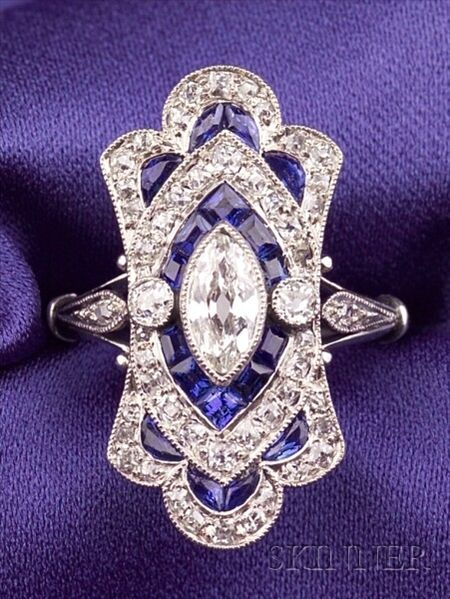 Art Deco Platinum, Sapphire, and Diamond Ring, bezel-set with an old marquise-cut diamond, further set with old mine-cut diamond melee, calibre-cut sapphire highlights, millegrain accents