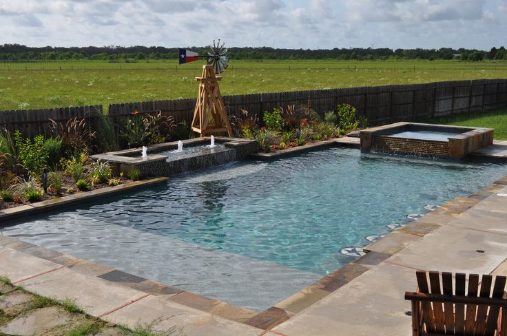 This southwest style rustic pool and spa features geometric design, raised basin with bubbler fountains, tiered spa dam wall, coping, and facing in flagstone, pebble interior, mosaic glass tile accents, swim up flagstone bar with custom Texas-star tile mosaic bar stools, umbrella sleeves, oversized tanning ledge, in-water bench seating, salt system, and bruched concrete deck.  Built in Rosharon, TX (southwest of Houston, TX) by Redman Pools, Inc. www.redmanpools.com