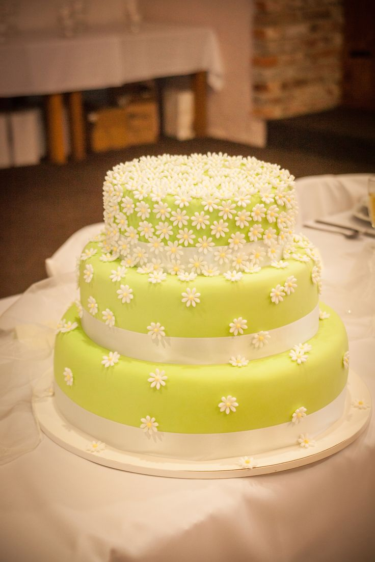 Třípatrový svatební dort potažený fondánem, dozdoben saténovými stuhami a fondánovými kytičkami.