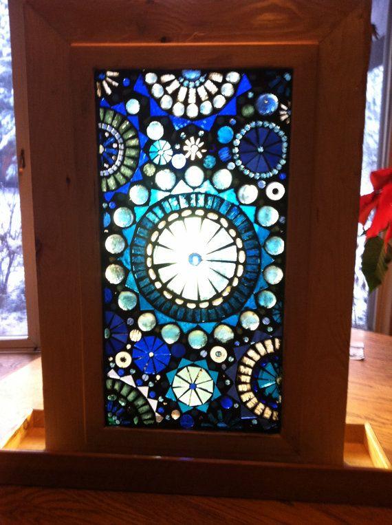 Me encanta hacer vidrio en mosaicos de vidrio. No sólo hacer me encanta el proceso de creación pero me encanta la manera en que transforman un lugar cuando aparece. Este panel fue creado con cientos de piezas de mano, corte vidrio, granos de cristal y gemas de vidrio. Varios matices de azul y transparente claro vidrio luz cuando iluminado por el sol. Este marco está diseñado para sentarse en la cima de mesa o el alféizar de la ventana. El marco mide 27 L x 18 W con una base que es de 5 ¼ W x…