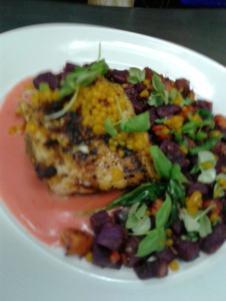 this is a pan seared grouper serve with purple Peruvian potatoes and yam hash wilted arugula and a strawberry beurre blanc topped off with passion fruit pearls