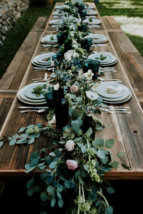 Long farm table, emerald green table garland, vintage bottles, pops of ivory and dusty blue | Image by Jessie Schultz Photography
