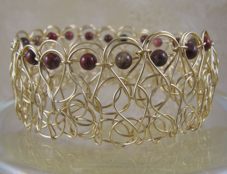Wide gold plated wire woven bangle with red jasper beads. Did a tutorial which I didn't like the results of so I folded it over and weaved the beads through. I didn't want to waste 15 ft. of wire!