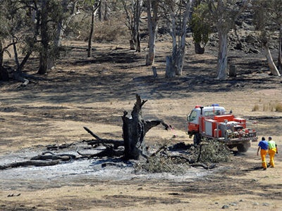 Firefighters work in a paddock blackened by recent bushfires near Bookham, New South Wales on 10 January, 2013.
