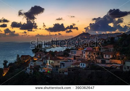 Aerial view of Funchal, capital city on Madeira Island. Beautiful town located in mountains with harbor and docked cruise ship during sunset (sky in red and yellow colors and blue clouds), Portugal.
