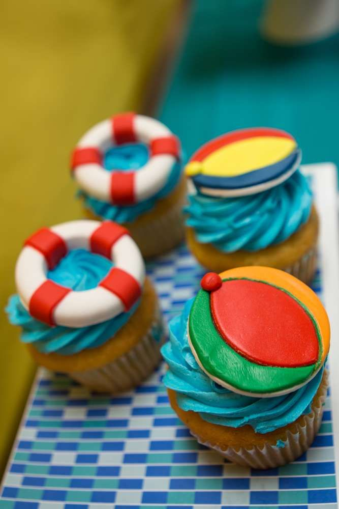 Beach ball and life preserver cupcakes at a pool birthday party! See more party planning ideas at CatchMyParty.com!