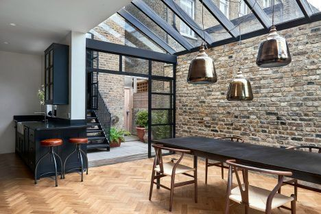 Inside this residential extension, oak parquet flooring, light-coloured brickwork and black-painted timber provide durable surfaces.