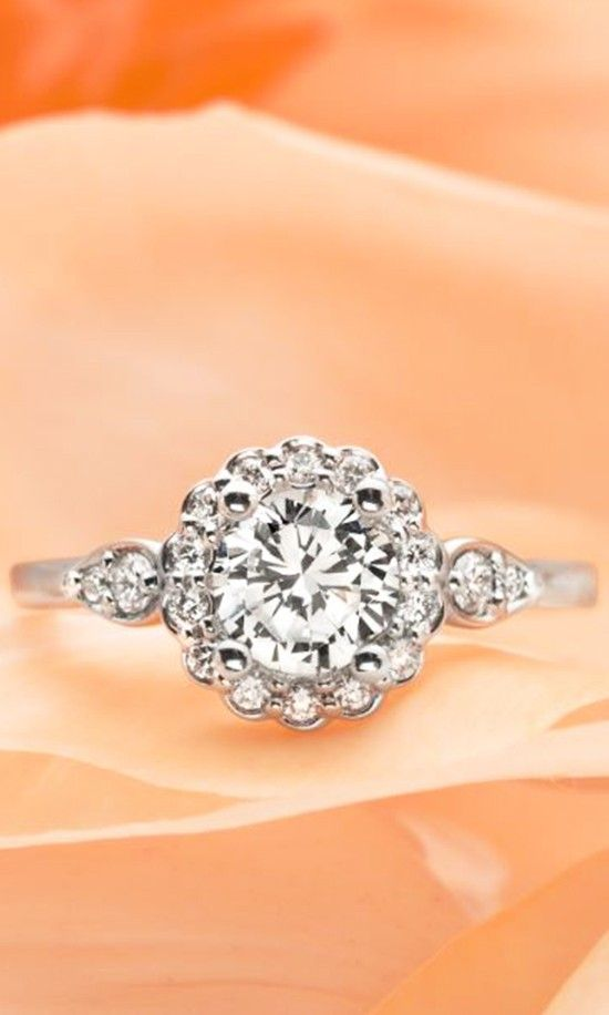 A dazzling halo of round diamonds encircles the center diamond to create a subtle floral effect.