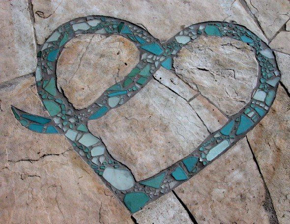 Stone landing detail of recycled glass mosaic inlaid in the shape of a heart.
