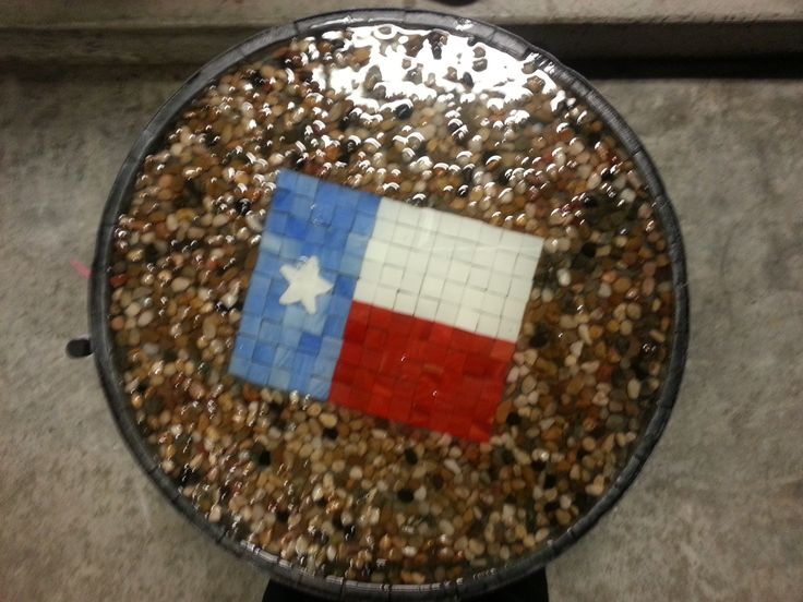 whiskey barrel table with Texas flag and rock insert. epoxy to hold it together and rubber spray paint under the rocks to avoid leaking
