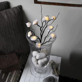 Denne flotte gren med smukke, hvide roser har i forhold til ægte roser den fordel, at de aldrig visner og, at man kan glæde sig over dem hele året rundt.